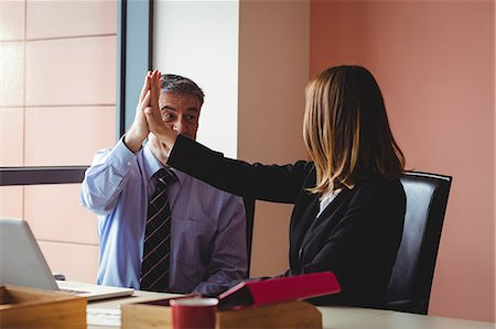 simsearch:6109-08700445,k - Businessman and businesswoman giving a high five in office Stock Photo - Premium Royalty-Free, Code: 6109-08701294