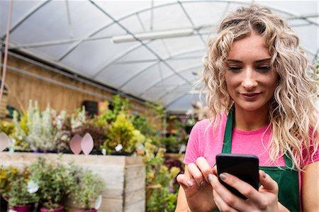 florist - Female florist using mobile phone in garden centre Stock Photo - Premium Royalty-Free, Code: 6109-08701223