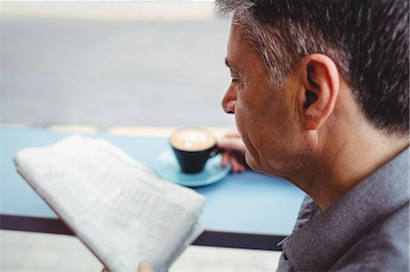 simsearch:6109-08700445,k - Close-up of man reading newspaper and holding coffee cup in cafeteria Stock Photo - Premium Royalty-Free, Code: 6109-08701354
