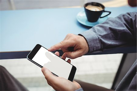 Close-up of man text messaging on mobile phone in cafeteria Stock Photo - Premium Royalty-Free, Code: 6109-08701381