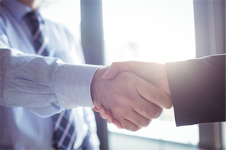 Businessman shaking hands with colleague in office Stock Photo - Premium Royalty-Free, Code: 6109-08701330