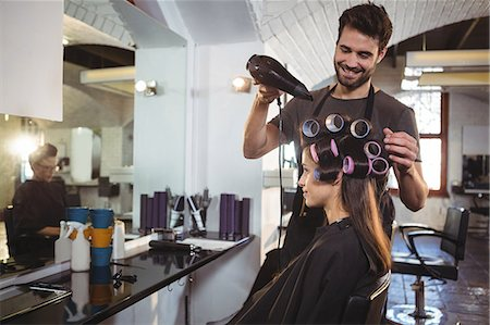Smiling male hairdresser styling customers hair at a salon Stock Photo - Premium Royalty-Free, Code: 6109-08705257