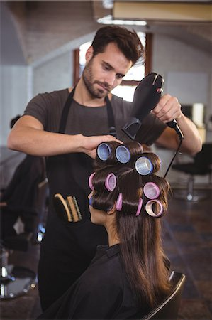 Male hairdresser styling customers hair at a salon Stock Photo - Premium Royalty-Free, Code: 6109-08705255