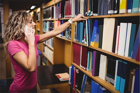 Woman talking on mobile phone while removing a book from bookshelf in library Stock Photo - Premium Royalty-Free, Code: 6109-08705346