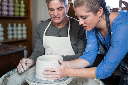 Male potter assisting female potter in pottery workshop Stock Photo - Premium Royalty-Free, Code: 6109-08705497
