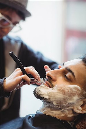 Man getting his beard shaved with razor in barber shop Stock Photo - Premium Royalty-Free, Code: 6109-08705410