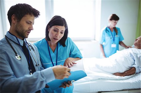 Male doctor and nurse interacting over a report in hospital Stock Photo - Premium Royalty-Free, Code: 6109-08720221