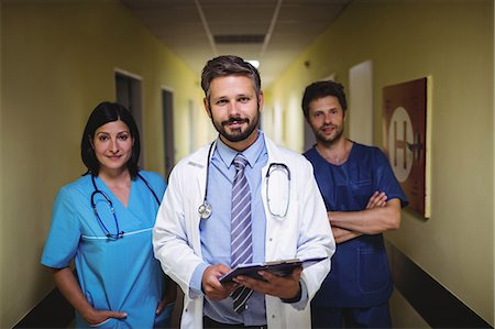 Portrait of doctor standing with nurse and ward boy in hospital corridor Stock Photo - Premium Royalty-Free, Code: 6109-08720335