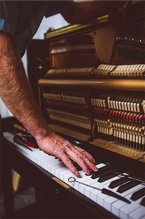 Piano technician repairing the piano at workshop Stock Photo - Premium Royalty-Free, Code: 6109-08720473