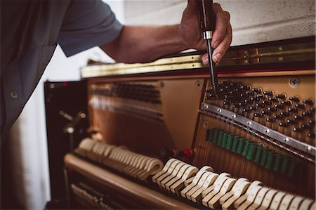 Piano technician repairing the piano at workshop Stock Photo - Premium Royalty-Free, Code: 6109-08720472