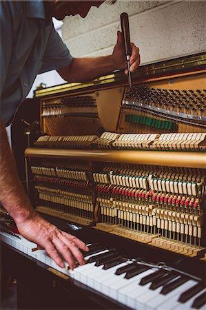 Piano technician repairing the piano at workshop Stock Photo - Premium Royalty-Free, Code: 6109-08720475