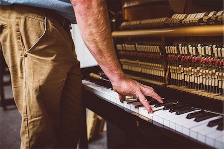 Piano technician repairing the piano at workshop Stock Photo - Premium Royalty-Free, Code: 6109-08720476