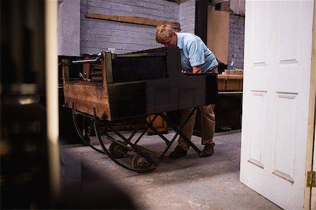 Piano technician repairing the piano at workshop Stock Photo - Premium Royalty-Free, Code: 6109-08720478