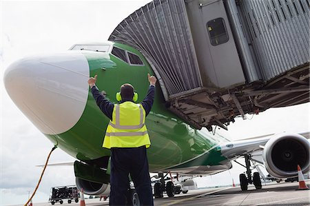 security - Rear view of airport ground crew worker directing airplane on runway Stock Photo - Premium Royalty-Free, Code: 6109-08722680