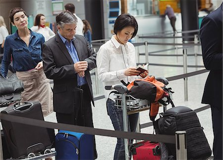 Passengers waiting in queue at a check-in counter with luggage inside the airport terminal Stock Photo - Premium Royalty-Free, Code: 6109-08722752