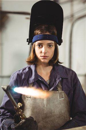 Female welder holding welding torch in workshop Stock Photo - Premium Royalty-Free, Code: 6109-08722902