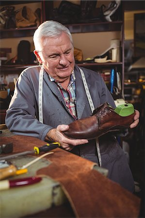 professional (pertains to traditional blue collar careers) - Shoemaker examining a shoe in workshop Stock Photo - Premium Royalty-Free, Code: 6109-08723020