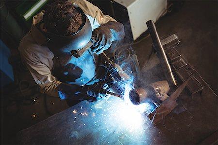 Welder welding a metal in workshop Stock Photo - Premium Royalty-Free, Code: 6109-08739071
