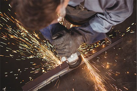 Welder cutting metal with electric tool in workshop Stock Photo - Premium Royalty-Free, Code: 6109-08739086