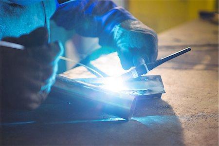 Welder welding a metal in workshop Stock Photo - Premium Royalty-Free, Code: 6109-08739154