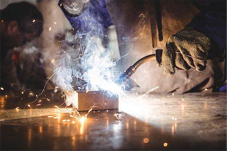 Welder welding a metal in workshop Stock Photo - Premium Royalty-Free, Code: 6109-08739138