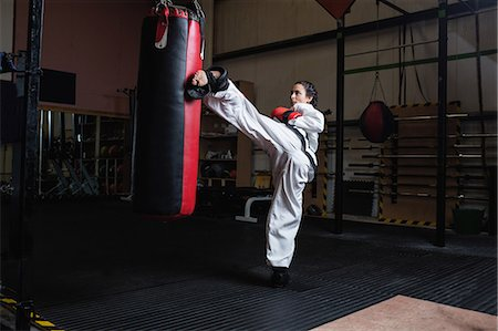 female - Woman practicing karate with punching bag in fitness studio Stock Photo - Premium Royalty-Free, Code: 6109-08739254