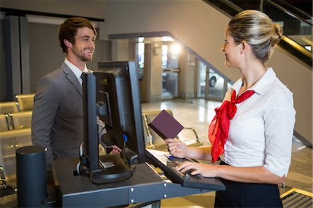 picture - Businessman interacting with female airport staff at the check in desk in airport terminal Stock Photo - Premium Royalty-Free, Code: 6109-08802682