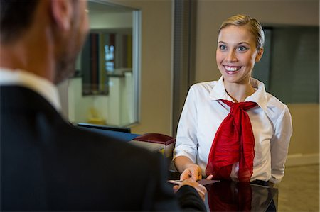 Female staff giving boarding pass to the businessman at the check in desk Stock Photo - Premium Royalty-Free, Code: 6109-08802726