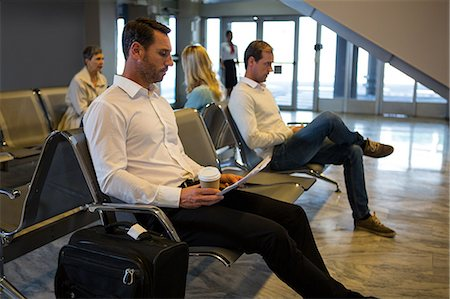 simsearch:6109-08700445,k - Businessman reading newspaper in waiting area at airport terminal Stock Photo - Premium Royalty-Free, Code: 6109-08802804