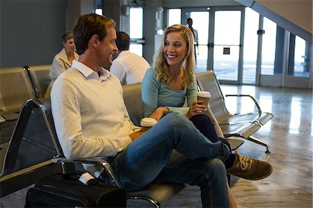 flying happy woman images - Happy couple sitting in the waiting area at airport terminal Stock Photo - Premium Royalty-Free, Code: 6109-08802805