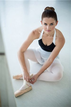 Portrait of ballerina wearing ballet shoes in the studio Stock Photo - Premium Royalty-Free, Code: 6109-08803059