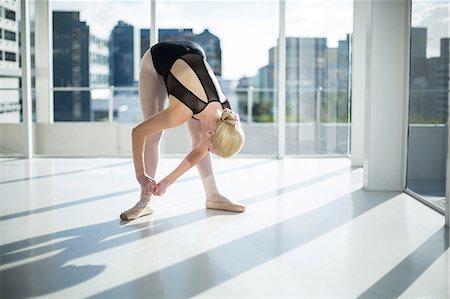 Ballerina tying her ballet shoes in the studio Stock Photo - Premium Royalty-Free, Code: 6109-08803086