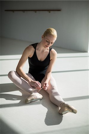 Ballerina tying her ballet shoes in the studio Stock Photo - Premium Royalty-Free, Code: 6109-08803088