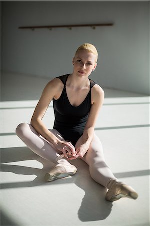 Portrait of ballerina tying her ballet shoes in the studio Stock Photo - Premium Royalty-Free, Code: 6109-08803089