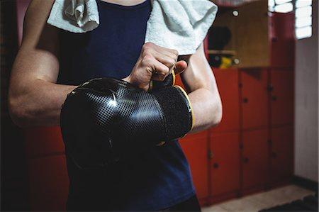Boxer wearing boxing gloves in locker room at fitness studio Stock Photo - Premium Royalty-Free, Code: 6109-08803769