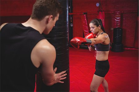 Female boxer practicing with trainer at fitness studio Stock Photo - Premium Royalty-Free, Code: 6109-08803731