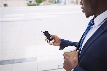 simsearch:6109-08700445,k - Mid section of businessman holding disposable coffee cup and using mobile phone outside office building Stock Photo - Premium Royalty-Free, Code: 6109-08804287