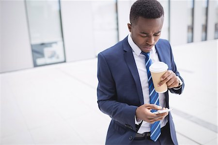 simsearch:6109-08700445,k - Businessman holding disposable coffee cup and using mobile phone outside office building Stock Photo - Premium Royalty-Free, Code: 6109-08804286