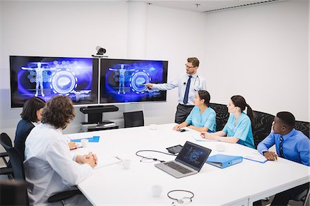 Doctor giving presentation to team of interim doctors at conference room Stock Photo - Premium Royalty-Free, Code: 6109-08804365