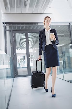 simsearch:6109-08700445,k - Businesswoman holding suitcase walking through office corridor Stock Photo - Premium Royalty-Free, Code: 6109-08804436