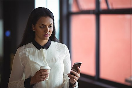 simsearch:6109-08700445,k - Businesswoman holding disposable coffee cup and using mobile phone in office Stock Photo - Premium Royalty-Free, Code: 6109-08805141