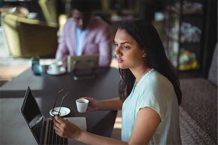 simsearch:6109-08700445,k - Thoughtful businesswoman holding coffee cup sitting at her desk in office Stock Photo - Premium Royalty-Free, Code: 6109-08805162