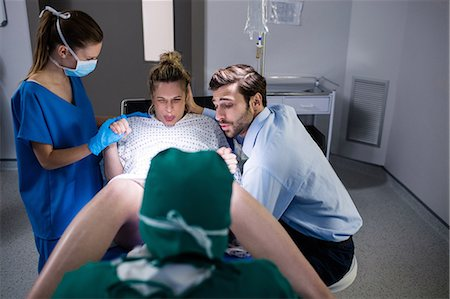 Doctor examining pregnant woman during delivery while man holding her hand in operating room Stock Photo - Premium Royalty-Free, Code: 6109-08830575