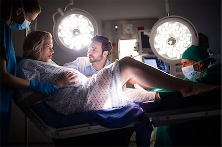 pregnant woman with doctor - Doctor examining pregnant woman during delivery while man holding her hand in operating room Stock Photo - Premium Royalty-Free, Code: 6109-08830578