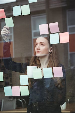 simsearch:6109-08700445,k - Business executive looking at sticky note while having cup of coffee Stock Photo - Premium Royalty-Free, Code: 6109-08830793