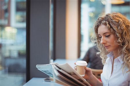 simsearch:6109-08700445,k - Woman reading newspaper while having coffee in cafeteria Stock Photo - Premium Royalty-Free, Code: 6109-08944304