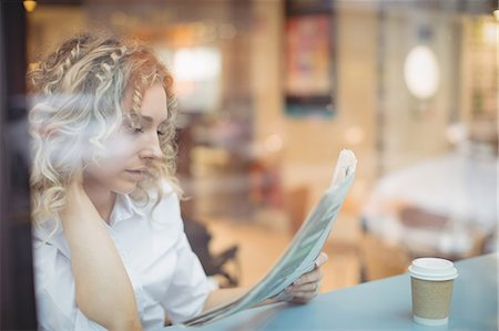 simsearch:6109-08700445,k - Woman reading newspaper at counter in cafeteria Stock Photo - Premium Royalty-Free, Code: 6109-08944306