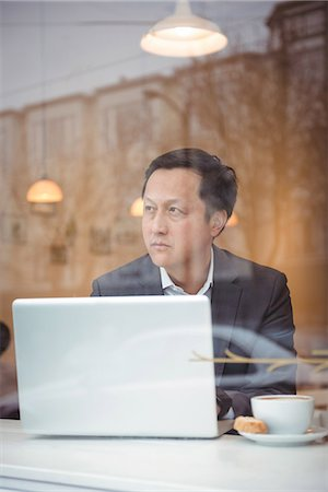 simsearch:6109-08700445,k - Thoughtful businessman using laptop in coffee shop Stock Photo - Premium Royalty-Free, Code: 6109-08945408