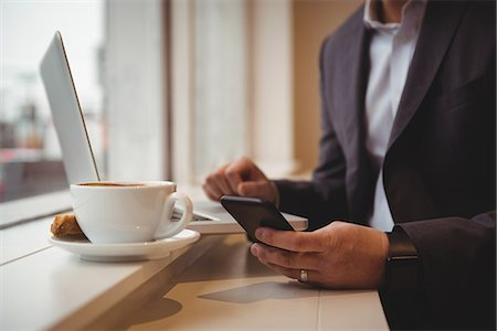 simsearch:6109-08700445,k - Midsection of businessman using mobile phone in coffee shop Stock Photo - Premium Royalty-Free, Code: 6109-08945409