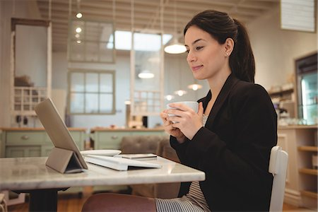 simsearch:6109-08700445,k - Businesswoman having coffee while looking at digital tablet in cafe Stock Photo - Premium Royalty-Free, Code: 6109-08945412